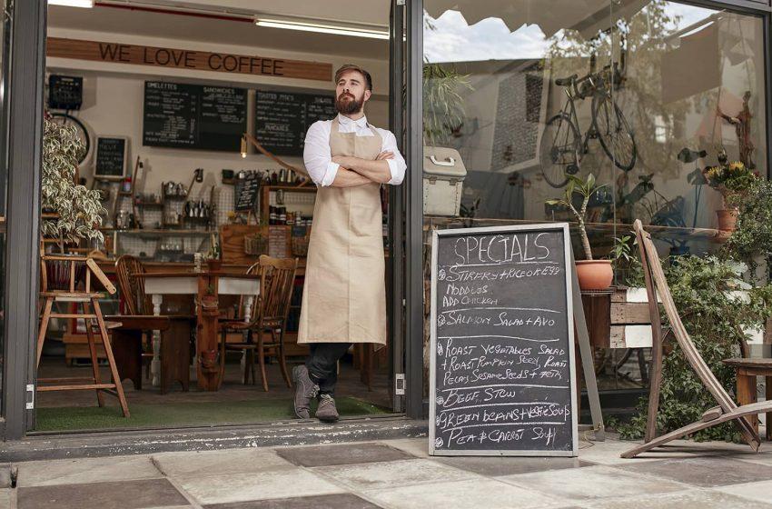 Barista standing in door of a coffee shop