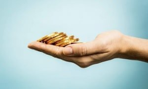 Hand holding golden coins concept on blue background. Business c