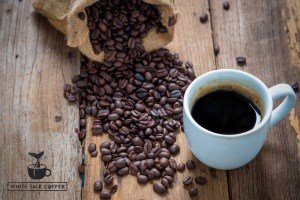 coffee cup and coffee beans on old wood background