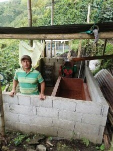 A coffee farmer participating in the Pro-Café project shows off his depulping equipment.